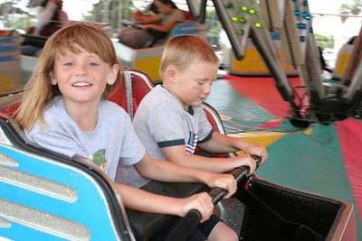 Sydney and Christopher enjoying a fast spinning ride at the Seabee Days carnival