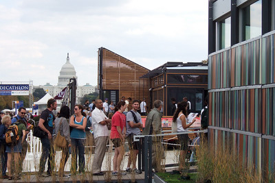 """The colorful University of Cincinnati house is on the immediate right and the Texas A&M """"groHome"""" is next down the Mall with the U.S. Capitol in the background. While the girls went shopping, Pat and Christopher headed to the National Mall to enjoy the 2007 Solar Decathlon, which joins twenty college and university teams in a competition to design, build, and operate the most attractive and energy-efficient solar-powered house. (Image taken with FinePix F10 at ISO 200, f7.1, 1/250 sec and 22.1mm)"""