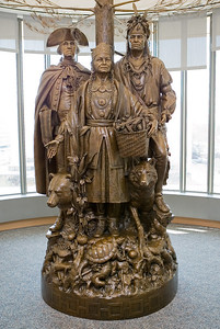Allies in War, Partners in Peace, 2004, by Edward Hlavka, St. George, Utah. Gift of the Oneida Indian Nation of New York.  This work honors the bonds of friendship that were forged between the Oneida Indian Nation and the fledgling U.S. during the American Revolution. Oneidas fought alongside the colonists in many key battles and helped sustain American soldiers during the darkest hours of the Revolutionary War. In the winter of 1777-78, a group of Oneidas walked more than 400 miles from Oneida Territory, in what is now central New York, to Valley Forge, Pennsylvania, carrying corn to feed starving soldiers. Polly Cooper, the Oneida woman depicted in the statue, taught the soldiers how to cook corn--one of the Three Sisters, the sustainers of life, along with beans and squash.  Oskanondonha, at right, played a key role in the Oneida Nation's decision to side with the colonists. Also known as Skenandoah, he was the wampum keeper and creator of government-to-government agreements, a highly respected individual among Oneidas.  General George Washington holds the two-row wampum belt, symbol of an agreement that the U.S. and the Oneida Nation would not interfere in the other's internal affairs.  Behind these figures stands the white pine tree, a symbol of peace, in the stories of the Oneida, Mohawk, Seneca, Onondaga, Cayuga and Tuscarora nations, which constitute the Haudenosaunee (Iroquois) Confederacy. Long ago, the Peacemaker united these warring nations with his message of the Great Law of Peace, unearthing the white pine tree and burying the weapons of war beneath its roots.   The turtle, wolf, and bear represent the three clans of the Oneida Nation.  National Museum of the American Indian