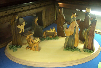 Ireland (made of wood). From the Sommer Collection at the Washington National Cathedral. This nativity set was made by Jilie D'arch of Puckhane Crafts, Ltd., Puckhane County, Tipperary. The two dimensional pieces are stained in natural tones, rather than painted, to let the grain of the wood show through. Note how the figures of the shepherd and the sheep he is carrying interlock. Annual Crèche Exhibit (nativity scenes) at the Washington National Cathedral. (Image taken with FinePix F10 at ISO 800, f2.8, 1/20 sec and 8mm)