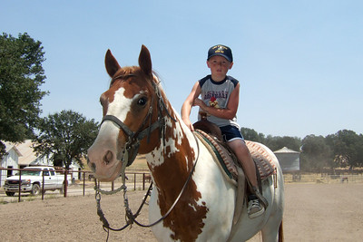 Christopher riding a horse in the arena on the Martinez family ranch.   We visited the Roth family our first weekend in California. The kids had a great time, especially on Sunday when Aunt Betsy and Uncle Frank took them for rides on the horses and four wheeler. (Image taken with FinePix F10 at ISO 200, f6.4, 1/600 sec and 8mm)