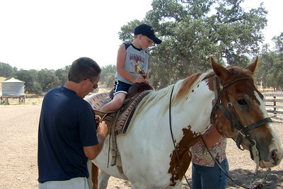 Pat and Aunt Betsy helping to shorten the stirrups so that Christopher can ride Joker.    We visited the Roth family our first weekend in California. The kids had a great time, especially on Sunday when Aunt Betsy and Uncle Frank took them for rides on the horses and four wheeler. (Image taken with FinePix F10 at ISO 200, f4.5, 1/450 sec and 8mm)