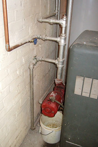 Boiler plumbing. The two pipes at the top are the returns from the 1st floor. The pipe in the middle is the basement return. (Image taken by Patrick R. Kane with FinePix F10 at ISO 800, f2.8, 1/100 sec and 8mm)