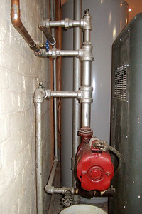 Boiler plumbing. The two pipes at the top are the returns from the 1st floor. The pipe in the middle is the basement return and the pipe at bottom with the valve is the cold water feed. (Image taken by Patrick R. Kane with FinePix F10 at ISO 800, f2.8, 1/100 sec and 8mm)