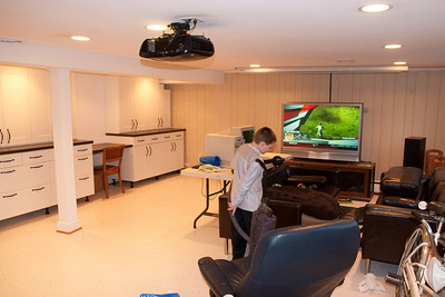 Christopher is helping clean up the mess. I shifted everything to one-side of the basement so that I could work on the cabinets. It's finally time to put things back. That's a HD projector in the middle of the ceiling and a 9-ft electric screen on the ceiling above the TV. (Image taken by Patrick R. Kane on 10 Jan 2010 with Canon EOS 20D at ISO 800, f4.0, 1/60 sec and 17mm)