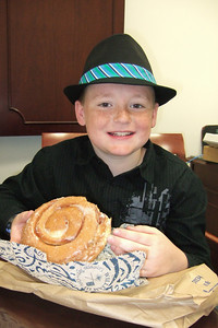 Christopher enjoying a huge donut in Pat's office at the Naval Facilities Engineering Command (NAVFAC) in the Washington Navy Yard. He skipped school this morning to see his dad receive the Navy Meritorious Civilian Service Award. (Image taken by Kathy T. Kane on 11 May 2010 with FinePix F10 at ISO 800, f2.8, 1/100 sec and 8mm)