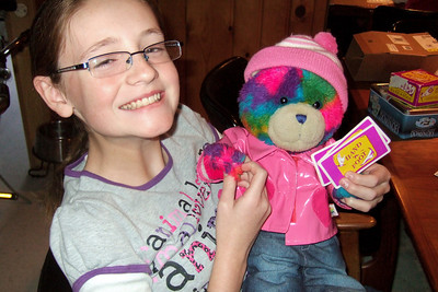 Sydney and Rainbow Bear playing Hand 'n Foot with Grandma and Grandpa (Image taken by Kathy T. Kane on 24 Nov 2010 with FinePix F10 at ISO 800, f2.8, 1/100 sec and 8mm)