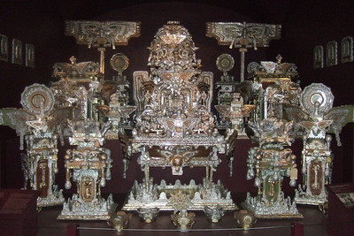 """""""The Throne of the Third Heaven of the Nations' Millennium General Assembly,"""" by James Hampton about 1950-64 from gold and silver aluminum foil, kraft paper, and plastic over wood furniture, paperboard and glass.  Little is known about James Hampton, despite the grandeur of his self-chosen title: """"Director, Special Projects for the State of Eternity."""" He was born in 1909 in Elloree, South Carolina, a small community of predominately African-American share-croppers and tenant farmers. His father, a gospel singer and self-ordained Baptist minister, left his wife and four children to pursue his itinerant calling.  In 1928 Hampton turned nineteen and moved to Washington, DC, to live with an older brother. Drafted into the Army in 1942, he served with a segragated unit that maintained airstrips in Saipan and Guam during World War II. Hampton returned to Washington in 1945 and worked as a janitor for the General Services Administration until his death in 1964.  Hampton was raised as a fundamentalist Baptist, but he disliked the concept of a denominational God and attended several churches in his northwest Washington neighborhood. As early as 1931, Hampton believed that he began receiving visions from God. It appears that by the time he returned from Guam in 1945 he had made one small, shrine-like object. This piece became part of his larger work and is now placed in front of the central tableau.  Smithsonian American Art Museum, Gift of Anonymous donors, 1970.353.1  (Image taken by Sydney J. Kane on 28 Nov 2010 with FinePix F10 at ISO 1250, f2.8, 1/100 sec and 8mm)"""