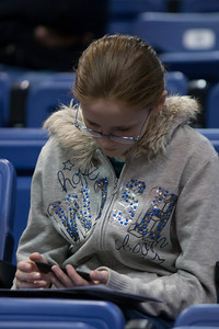 Sydney playing on Christopher's iPod Touch before the American University and Holy Cross women's basketball game. The Eagles beat the Crusaders 84 to 53. (Image taken by Patrick R. Kane on 22 Jan 2011 with Canon EOS-1D Mark III at ISO 1600, f2.8, 1/320 sec and 200mm)