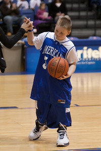 Christopher getting a high five after winning a competition during a time-out in the American University and Holy Cross women's basketball game. Christopher and Nick had to go from one end of the court to the other, getting dressed along the way in extra large shorts, a jersey and shoes, then finish with a layup. Christopher finished first and then watched the Eagles beat the Crusaders 84 to 53. (Image taken by Patrick R. Kane on 22 Jan 2011 with Canon EOS-1D Mark III at ISO 1600, f2.8, 1/320 sec and 120mm)