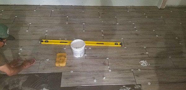 The floor tile, which is the same as what Andrew had installed at his house, is being installed in the downstairs efficiency, 1123 E Cedar St, Rockport, Texas, April 29, 2020