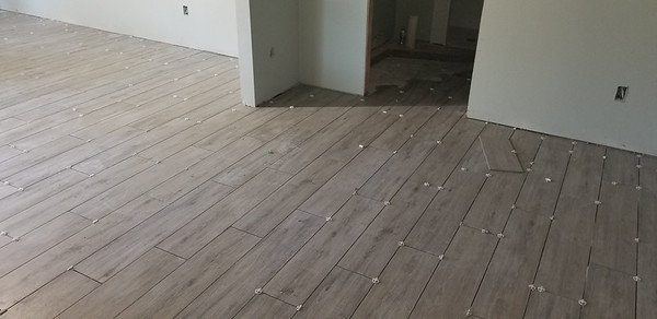 The floor tile, which is the same as what Andrew had installed at his house, is being installed in the downstairs efficiency, 1123 E Cedar St, Rockport, Texas, April 30, 2020