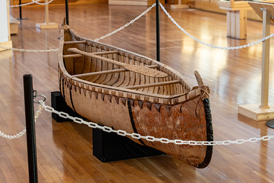 Birch Bark Canoe made by Larry Godfrey, Sault Sainte Marie Tribe of Chippewa. This handmade birch bark canoe is sealed with pine pitch and treated with bear grease in order to hold out water. The wood is treated with ash for color, and hand burnt with decorative finials at the bow and stern. The canoe has a hand carved paddle with burnt inlay designs. Crazy Horse Memorial, Crazy Horse, South Dakota