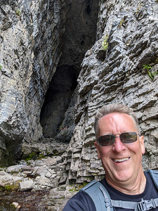 Patrick Kane in front of Wind Cave. The opening is huge and narrows down to a small passageway approximately 30-yards into the cave. There was a strong, cold wind blowing out of the cave. 6.3-mile hike on the Darby Canyon Wind Cave Trail, Alta, Wyoming