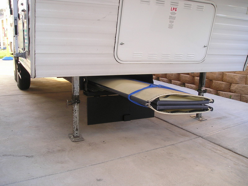 """PORTA-BOTE STORAGE (Mar 2004)  To transport our 10-ft Porta-Bote, I built an inexpensive undercarriage storage unit for our 5th wheel trailer. I used two 12-ft galvanized roofing panels to protect the boat from road debris. The panels are supported at the front and in the middle by angle irons (bent into a U-shape and bolted to the frame) and at the rear by the axle. A hinged plywood door covers the front opening.  See more photos in the <A HREF=""""http://kanefamily.smugmug.com/gallery/3859527"""">photo album</A>"""