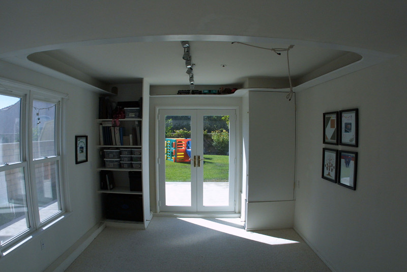 """Hobby Room (Jan-Jul 2000). This project took a long time to get off the drawing board, especially since Pat was planning on doing the majority of the work. The hobby room is a partial garage conversion that changed an L-shaped three car garage into a standard two car garage plus a bonus room. To let in light and provide better access to the yard, Pat installed double-hung windows and French doors. He also enclosed the hot water heater and added shelves for Kathy to store her Creative Memories products.  <A HREF=""""http://kanefamily.smugmug.com/gallery/3845363"""">Photo Album</A>"""