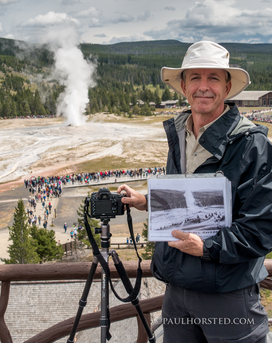 Paul re-photographing historic photo from roof of Old Faithful Inn, Old Faithful erupting in background, Yellowstone National Park.