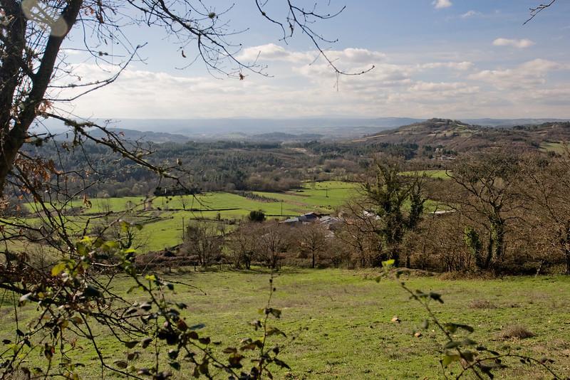 La vista desde la carretera mirando hacia la pequeña aldea de Santa María del Pinel (detrás de los árboles).  En la distancia se ven los montes.  Detrás de estos se encuentra Monforte de Lemos, y más allá, Santiago de Compostela.