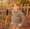 Kieran in school uniform digging outside (30-9-86)