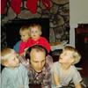 Dec. 24, 1980<br /> 1104 W. 680 S. Orem, UT<br /> Johnny, Teresa, JaiAnn, Joe & Jacob Meakin reading a book.