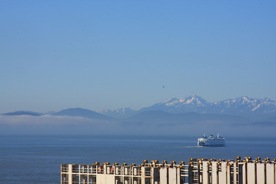 Shot of the Olympic Mountains with a ferry and fog on the water.