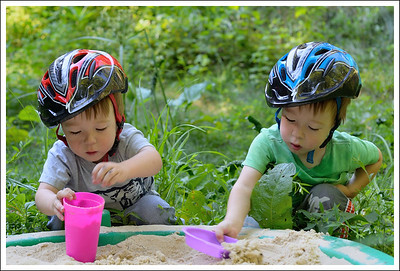 Busy boys run from one activity (strider bicycles) to sandbox.