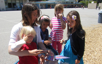 Rachel reading to the girls at the school playground