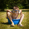 Boy wearing swimming mask sitting in a washbowl on a hot summer day