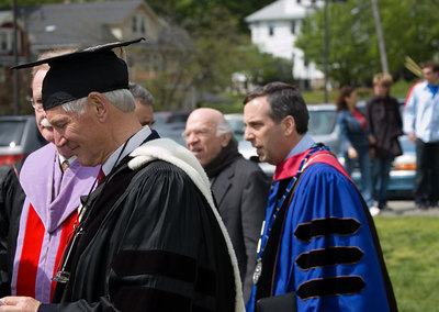 President Bacow (blue robe) and other faculty entering Saturday's  Baccalaureate Service in tent.