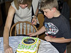 Alex assisting with the cutting of the cake.