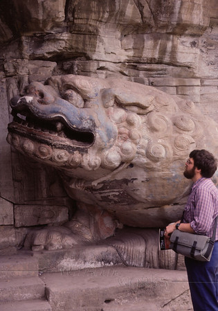 Rob with the lion guarding the Grotto of Full Enlightenment at Baoding Shan, near Dazu.The lion is associated with WenShu (aka Manjusri), the Bodhisattva of Wisdom. The carvings at this site date from the 12th century (Song Dynasty).