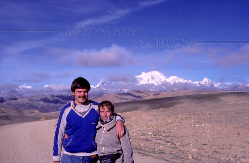 """Us (Rob and Anna Lisa) on the Tibetan plateau....our bus had just rounded a bend and the entire Himalayan vista was breathtakingly spread out before us! The main peak behind us is Shishapangma, which in Tibetan means """"rest above the grassy plains"""". Its Sanskrit name is Gosainthan, """"abode of God"""". It's one of the """"8,000s"""" -- peaks above 8,0000 meters."""