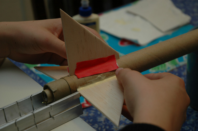 Balsa wood fins are glued to rocket.