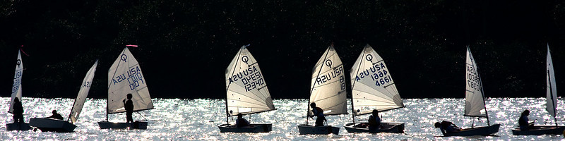 One child is standing having a drink, another is looking at something in the water -each one of these little sailboats could have been its own great photograph because of all the different poses.