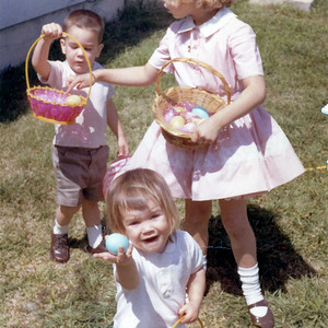 Kathy Kane showing off her Easter egg with her brother, John, in the background getting help from Cindy, on Easter Day, March 29, 1964. Gray Drive, Killeen, Texas?