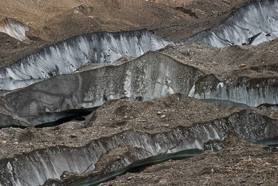 Meltwater streams cutting channels in the glacier, exposing bare ice.