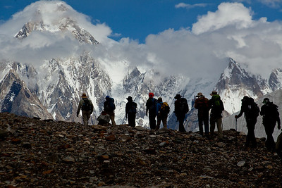 Our group slowly marches as Gasherbrum IV, 7925 m (26,001 ft)comes into dramatic view with the clouds slowly parting.