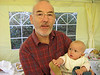 Dad holding Mae at her naming day.