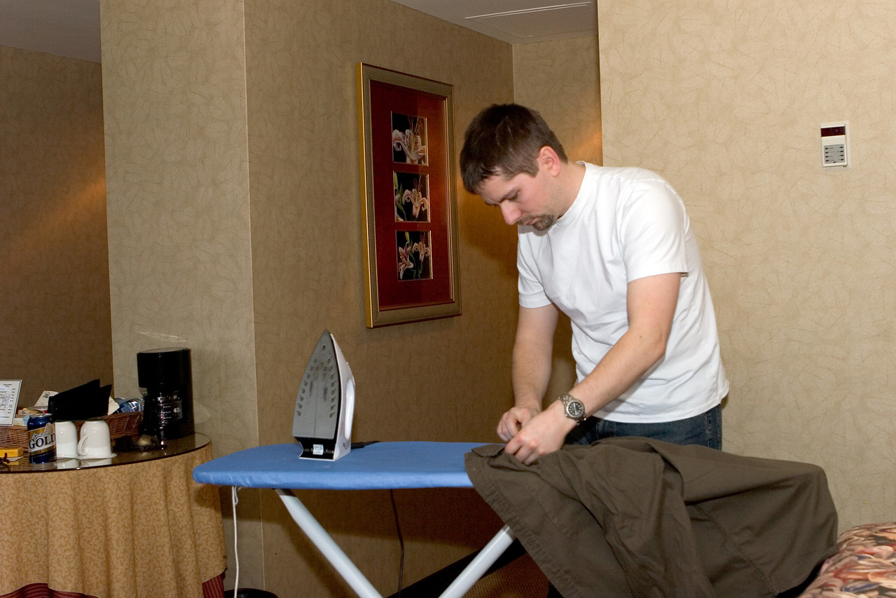 Trying to look good by ironing his shirts.