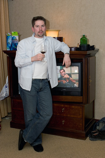 Uhler posing in front of a TV playing Commando. Note the Jag in the back and the black slippers.
