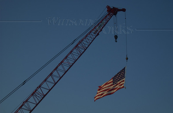American flag flying at Highlands Bridge construction site, dusk