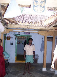 "This man is standing under the roof ""funnel"".  Taffy is also under the roof, and the washwater pool collecter is on the floorYou can see how think the roof is, thhough it is out of focus.  These are the old style buildings."