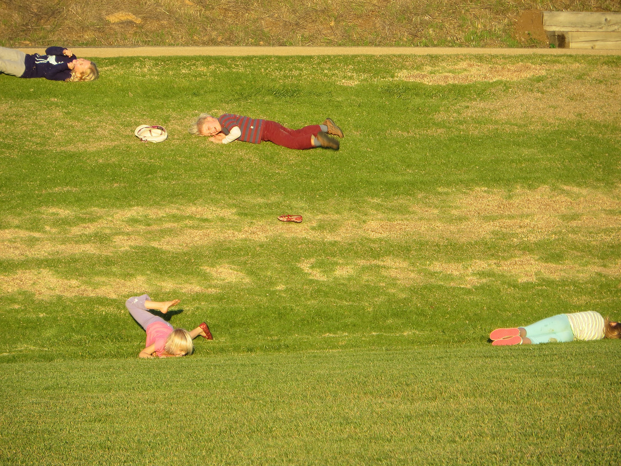 All four kids rolling down a hill.