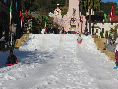 Sofia sliding down snow hill (snow over a base of hay) at San Rafael winter festival