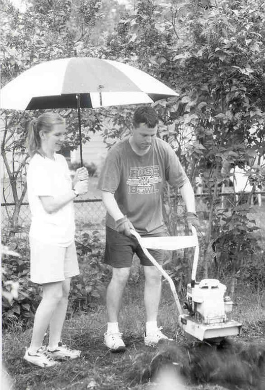 Yard work, in the rain, but just like post office workers, neither rain nor sleet.....   Garden rototilling was finished, and even planted.  Now if only tomatoes escape the cut worms.  6-2005.