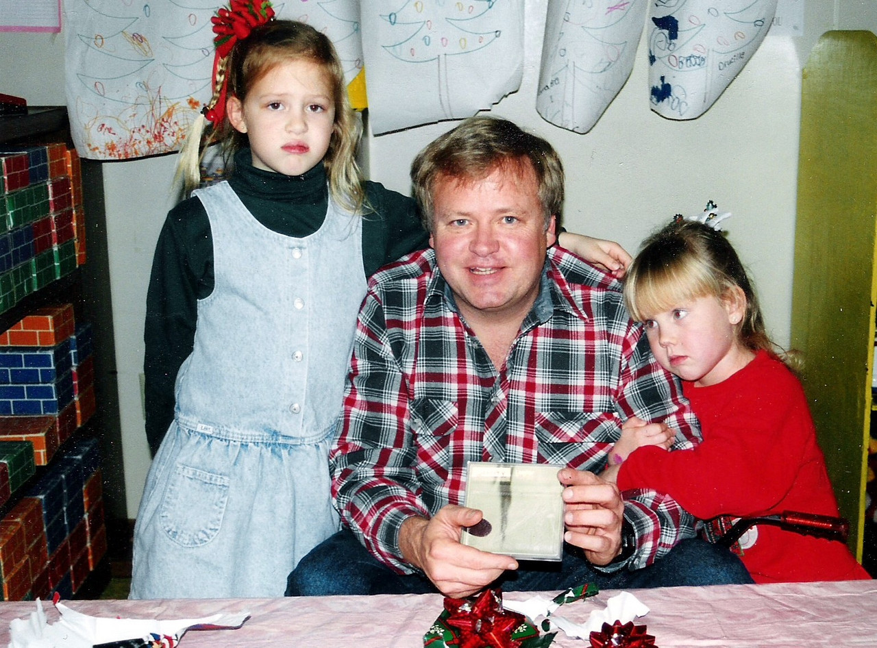 Trying to be happy in some sad times.  Sarah Jane, Dad, and Katie.  Looks to be at Christmas going by the drawings on the wall, presents, etc.  I tried hard to take car of my kids, and they took care of Dad.