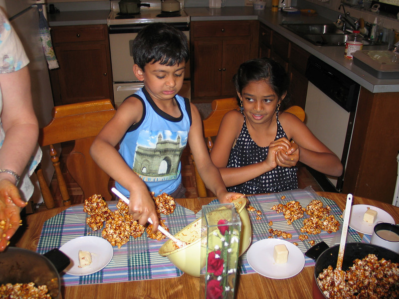 Making popcorn balls!  Rithik and Resya like the gooey fun!