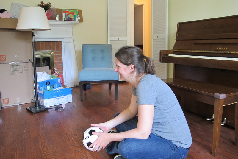 Liz and Jim moved into their new house in Kensington on May 12.  We watched Carter and Charlotte during the move and brought them to the new house after the movers had left.  This is Liz in her new living room preparing to roll a ball to Charlotte.