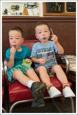 The boys get a treat if they sit quietly while getting their hair cut, so they do.