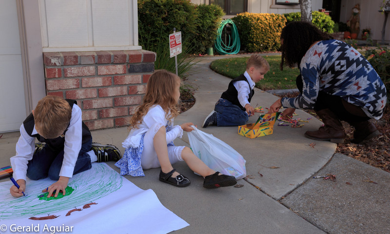 Kyle, Ellie, and Eli doing some drawing in the front of the house and getting some assistance from Amanda.